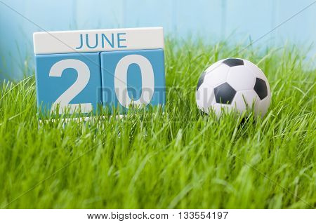 June 20th. Image of june 20 wooden color calendar on green grass background with football outfit. Summer day.