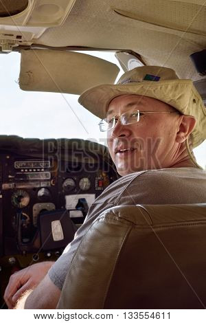 Pleased man in the cockpit of a small airplane. Flying over the desert is one of the most popular tourist attractions in Namibia