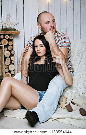 beautiful couple hugging sitting in a cozy atmosphere. man looking away and think about something