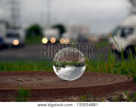 Transparent ball on the hatch near the roadway. Evening lights of cars. In the bowl of a reflection of the electrical towers. Concepts, ideas - Urban ecology, traffic safety. Clean City, electrician, harmful emissions