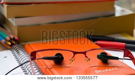 the school, things for school lie on paper, variety, different objects, eye eyepieces, earphones from a player, be engaged with music