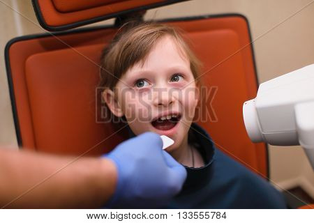 close up of dentist putting intraoral shield to female patient mouth and assistant directing x-ray machine at dental clinic