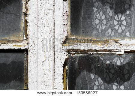 Close up view of an old exterior window frame with cracked and chipping white paint as lacy curtains hang behind it