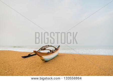 Fishing boat resting on empty beach in Sri Lanka