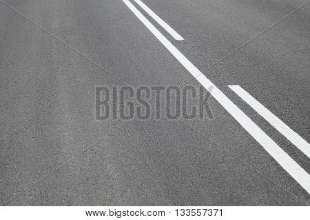 Abstract close up image of paved road with black tarred surface and white painted dividing lines to indicate driving lanes