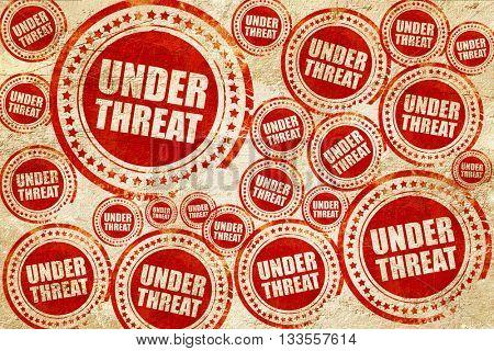 under threat, red stamp on a grunge paper texture
