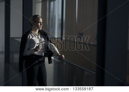Strong confident business woman standing in an dark office building hallway