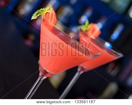 Two Strawberry Daiquiri cocktails shot on a bar counter