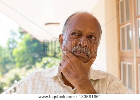 Closeup portrait upset elderly pensioner hands on face looking up thinking deeply isolated outside outdoors background