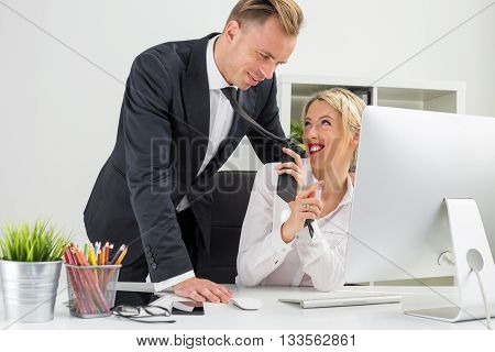Woman flirting with her co-worker and pulling his tie