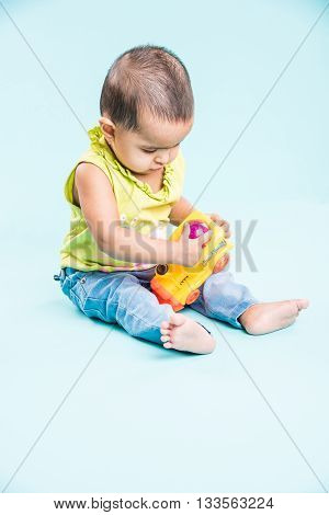indian child playing with colourful toy. Isolated on blue background, indian girl playing with engine toy, asian girl playing with colourful toy engine