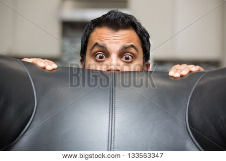 Closeup portrait grown young man hiding behind black leather couch afraid and worried isolated indoors background