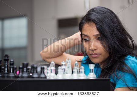 Closeup portrait thinking woman in blue shirt playing chess wondering next move isolated indoors background