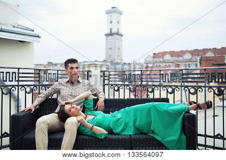 Couple relaxing on the terrace balcony with beautiful scenery on the ancient city. Brunette guy in a beige shirt and trousers sitting on the couch with a girl who lying him kneeling in a green dress.