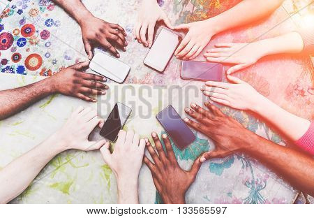 Group of friends having fun with smartphones - Closeup of multiracial hands social networking with mobile cellphones - Technology and phone addiction concept - Soft focus on hands - Vintage filter