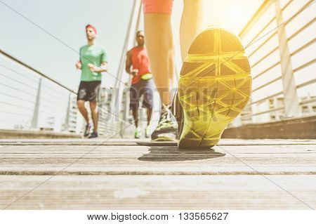 Multiracial friends running on urban bridge with back light - Fitness people make jogging in city contest on summer day - Healthy lifestyle concept - Focus on foot toe - Retro desaturated filter