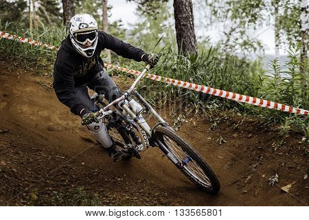 Miass Russia - May 29 2016: man athlete mountain biking around sharp turn in forest during Cup