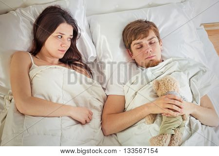 man with childish behavior sleeping in bed