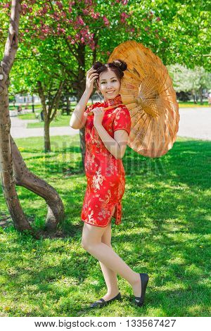 Beautiful Asian Girl In Traditional Chinese Red Dress With Bamboo Umbrella.