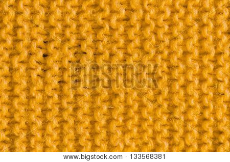 Close up the texture of knitted yellow cloth.