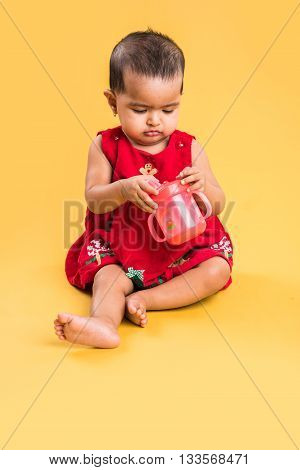 indian baby girl with sipper or water bottle, indian infant with bottle or sipper, asian infant, isolated over yellow background