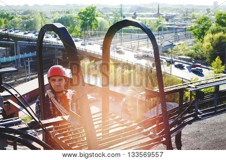 Industrial climber climbs to the roof of the building. work at height. worker on the background of the bustling city, the railway station and overpass