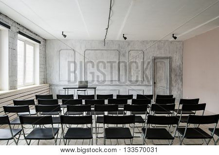 Room for lecture with a lot of dark chairs. Walls are white, loft interior. On the right there is a door. On the background there is a table with a laptop