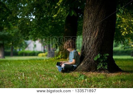 The boy of 8-9 years sits under a big tree having inclined over the tablet. The child in earphones with enthusiasm looks at the screen. He sits sideways to a camera.