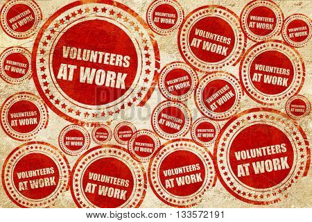 volunteer at work, red stamp on a grunge paper texture
