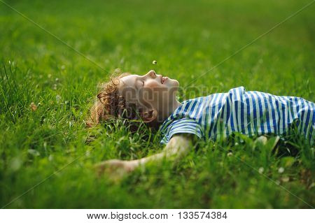 The boy of 8-9 years lies in the field on a green grass. He has stretched hands in the parties. In a mouth a floret. Eyes are closed from pleasure. Blond curly hair. On cheeks a flush.