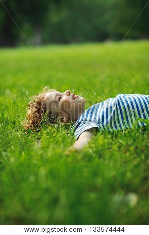 The little boy lies on a green lawn in park. He has stretched hands in the parties. In a mouth a floret. Eyes pensively look up. Blond curly hair. On cheeks a flush.