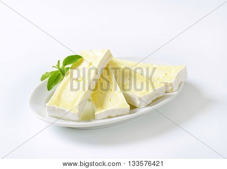 plate of sliced soft cheese with white rind on white background