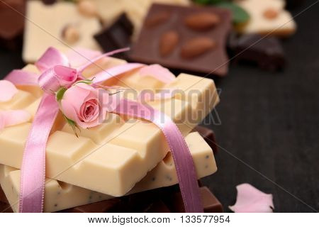 Chocolate tied with pink ribbon on black background