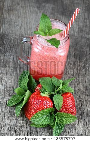 Strawberry smoothie with mint on a woden background