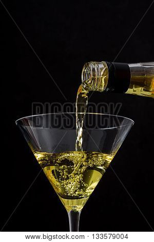 Bottle pouring liqueur into a glass on black background