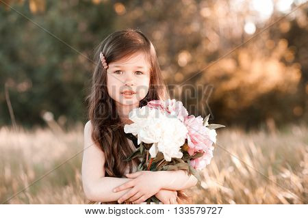 Cute baby girl 4-5 year old holding flowers in field. Looking at camera. Childhood.