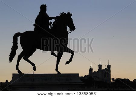 LYON, FRANCE - MAY 16, 2013: This is statue of Louis 14 and the Basilica of Notre Dame de Fourviere in Lyon sunset sky.