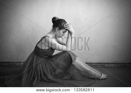 Depressed woman in a ballet dress sitting on the floor.