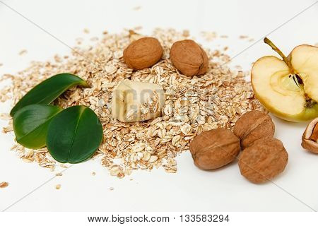 There are Banana,Apple with Walnuts and Rolled Oats,Wooden Trivet,with Green Leaves,Healthy Fresh Organic Food on the White Background,Selective Focus