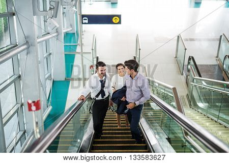 Group of businesspeople ride the escalator and talking.