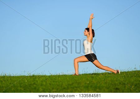 Woman doing pilates and yoga stretching exercise. Healthy sporty girl exercising outdoor.