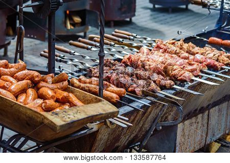 Grill sausages in a wooden trough and meat on skewers. Ukrainian festive fairs
