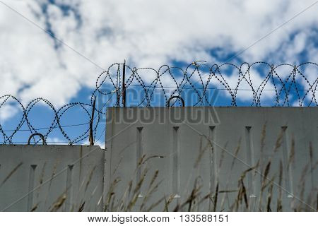 Grass In The Background Concrete Fence With Barbed Wire And Sky Clouds