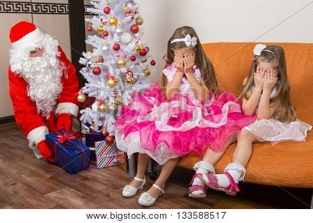 Two Girls Closed Eyes With His Hands Until Santa Claus Put Presents Under The Christmas Tree