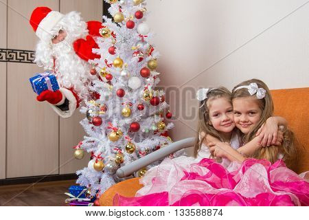 Two Girls Hug On The Couch, Santa Claus Peeping From Behind Trees