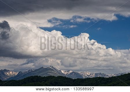 Mountain ridge with snow and blue sky with spectacular clouds in Epirus, Greece