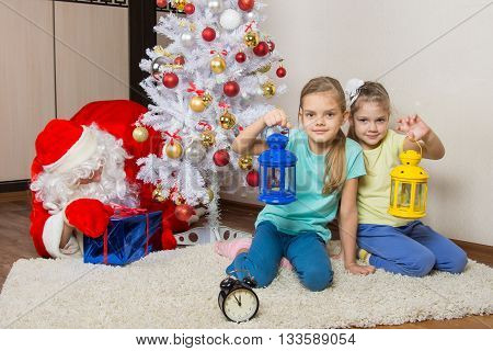 Two Girls With Flashlights Waiting For Santa Claus At The Christmas Tree In New Years Eve