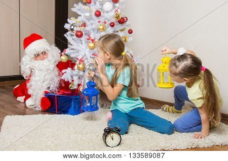 Two Girls With Flashlights To See Santa Claus Who Was Trying To Discreetly Put The Presents Under Th