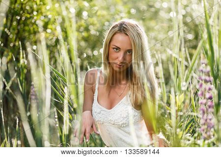 Blond young woman in a grass close-up.