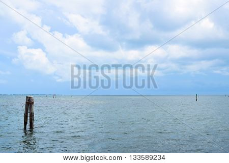 Rustic abandoned dock in the vast Atlantic Ocean beyond with clouds above